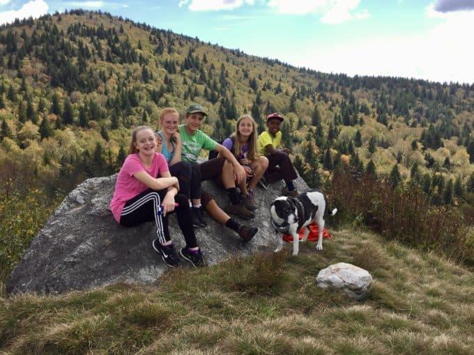 Kids on rock in meadow